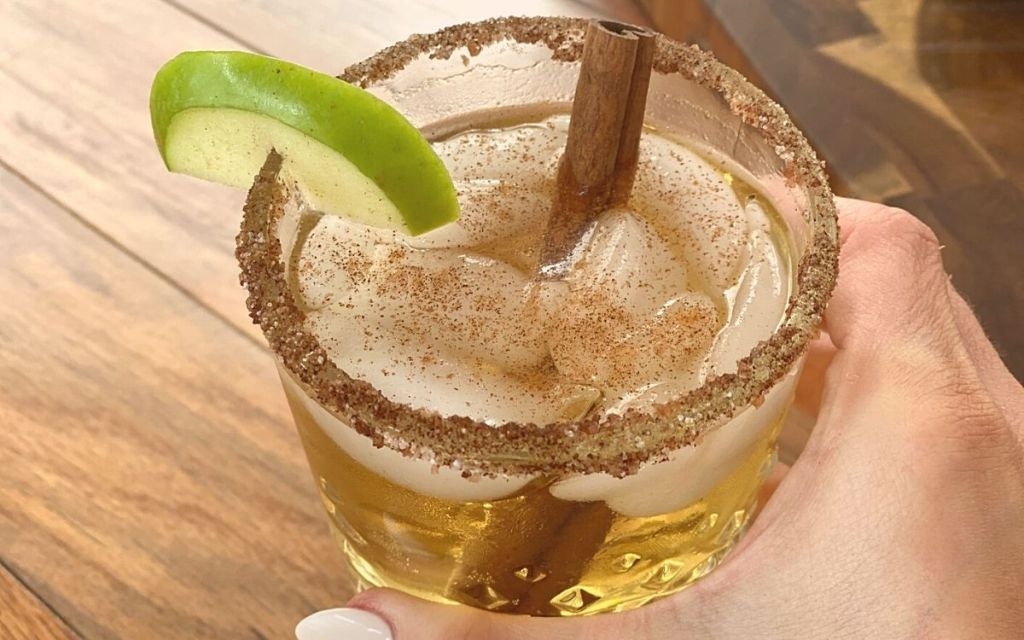 A hand holding a drink with cinnamon sticks and an apple slice on the rim