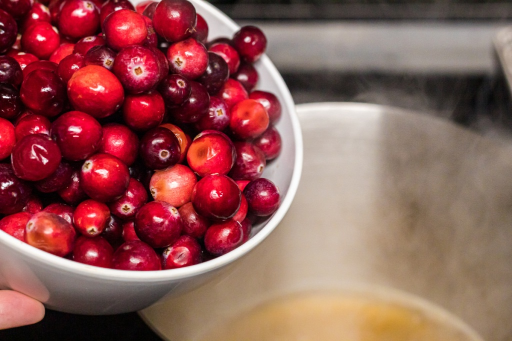 pouring cranberries into saucepan