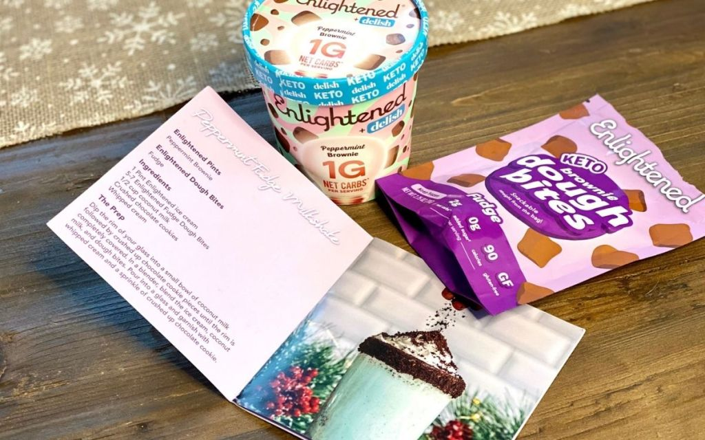 some ice cream and dough bites next to a recipe book on a table
