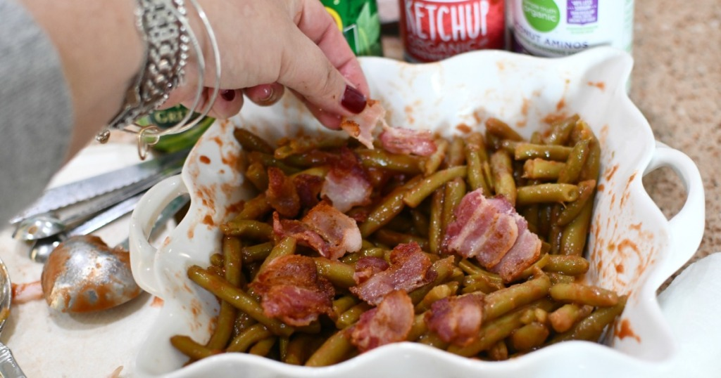 adding bacon to green beans in a casserole dish