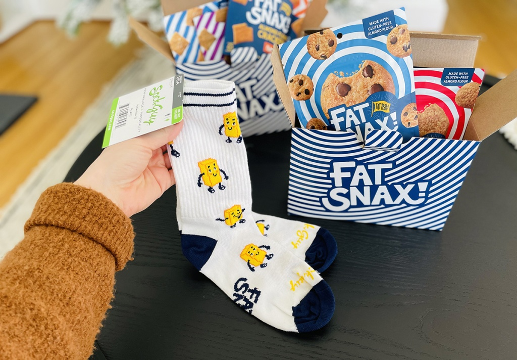 holding pair of socks with butter design