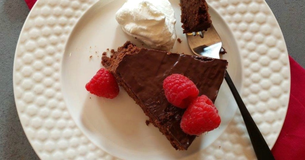 rich slice of keto chocolate cake with raspberries on top