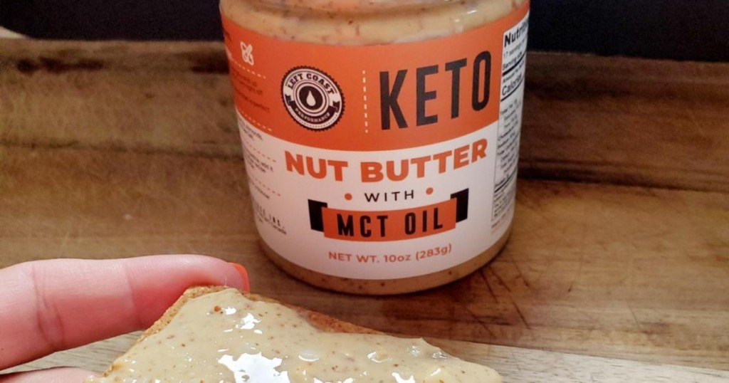 holding cracker with keto nut butter on top