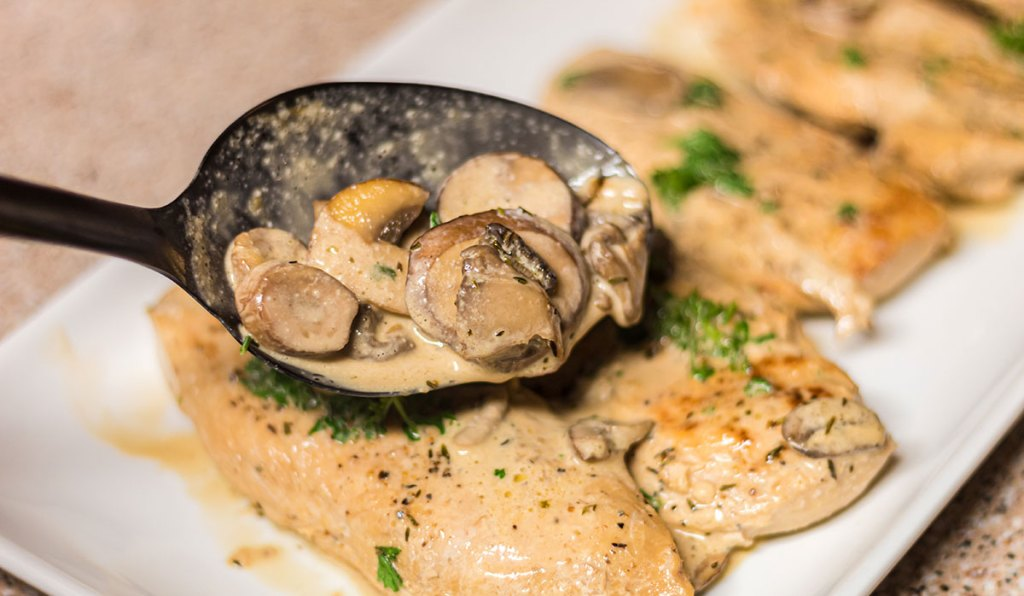 spooning mushrooms and sauce over keto chicken marsala