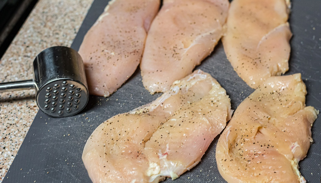 chicken breast with meat mallet after being tenderized