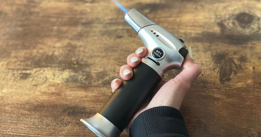 A hand holding a blow torch