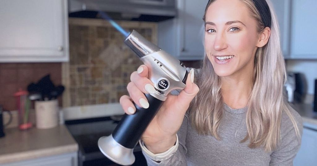 A woman holding a blow torch in a kitchen