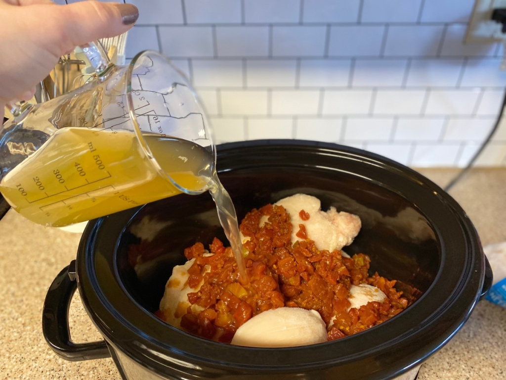 pouring chicken broth into slow cooker