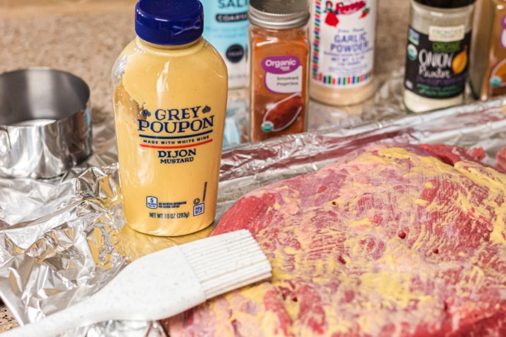 spreading dijon mustard over brisket