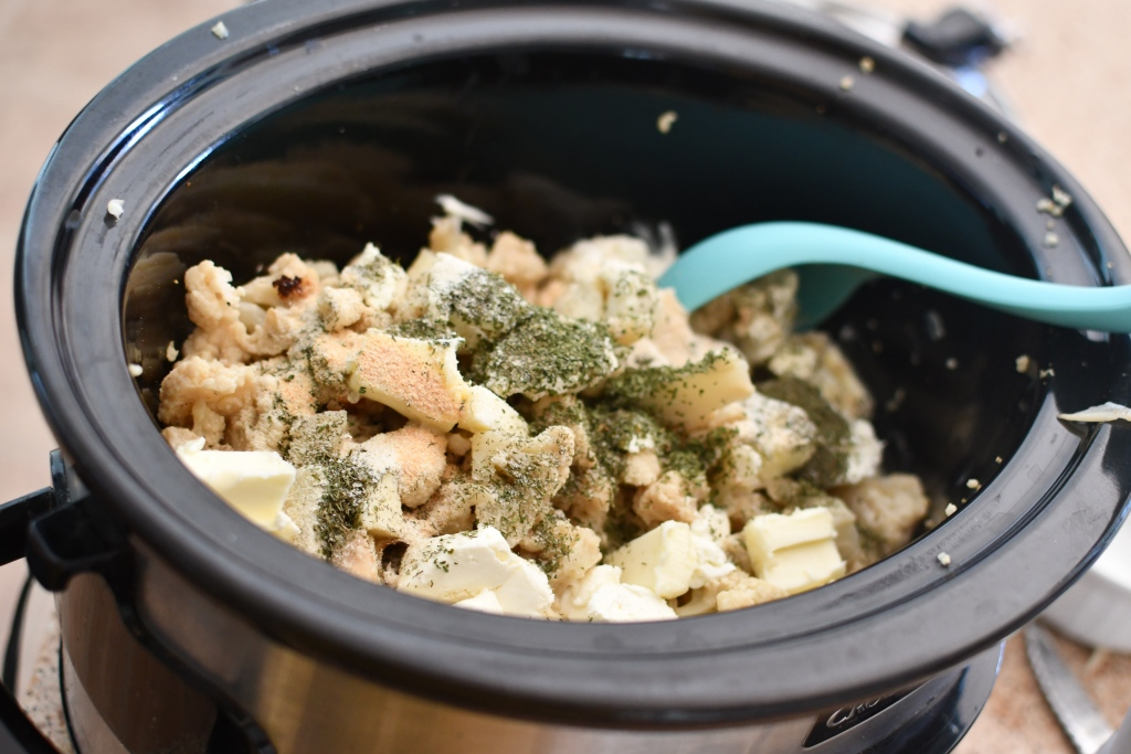 cauliflower inside slow cooker with cream cheese and seasonings