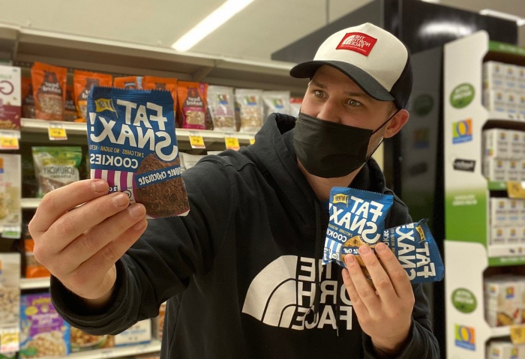 man holding fat snax cookies in store aisle