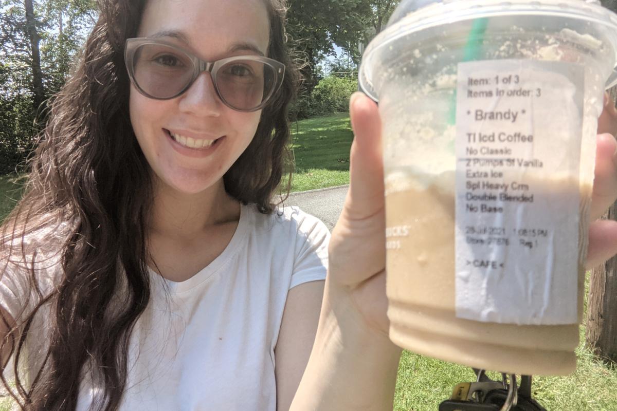 Woman holding keto frappuccino outside
