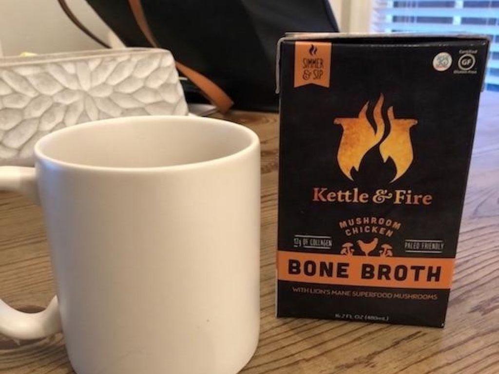 carton of bone broth next to mug