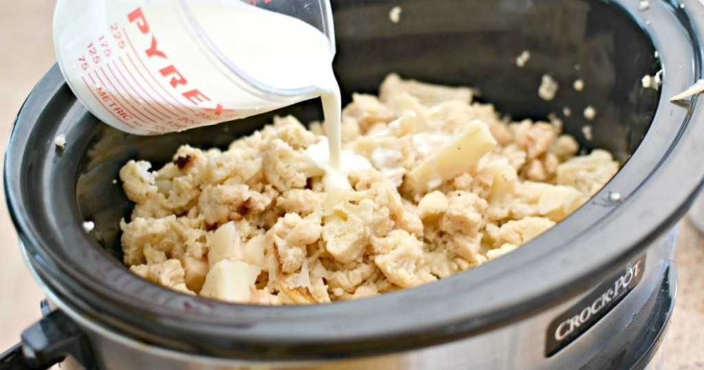 pouring cream over cooked cauliflower inside slow cooker