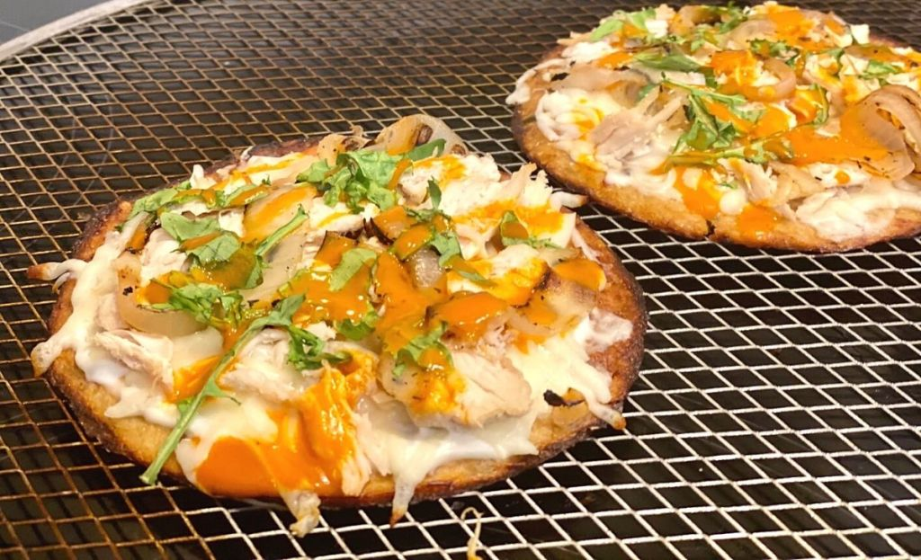 Two flatbreads on a pizza pan