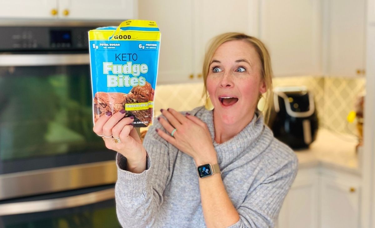 A woman holding a bag of fudge bites and making a happy face