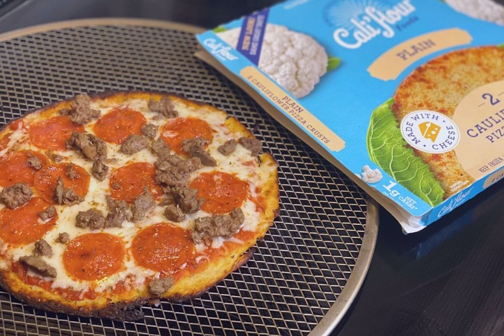 A pepperoni and sausage pizza on a pan next to a pizza crust box