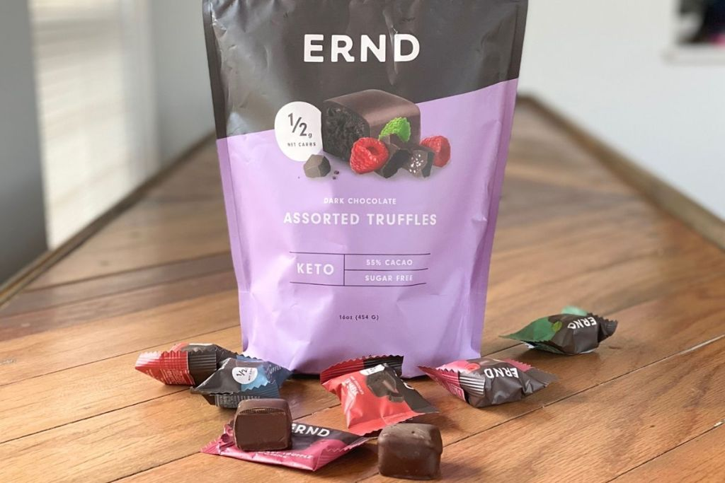 A bag of chocolates on a counter next to some wrapped chocolate pieces
