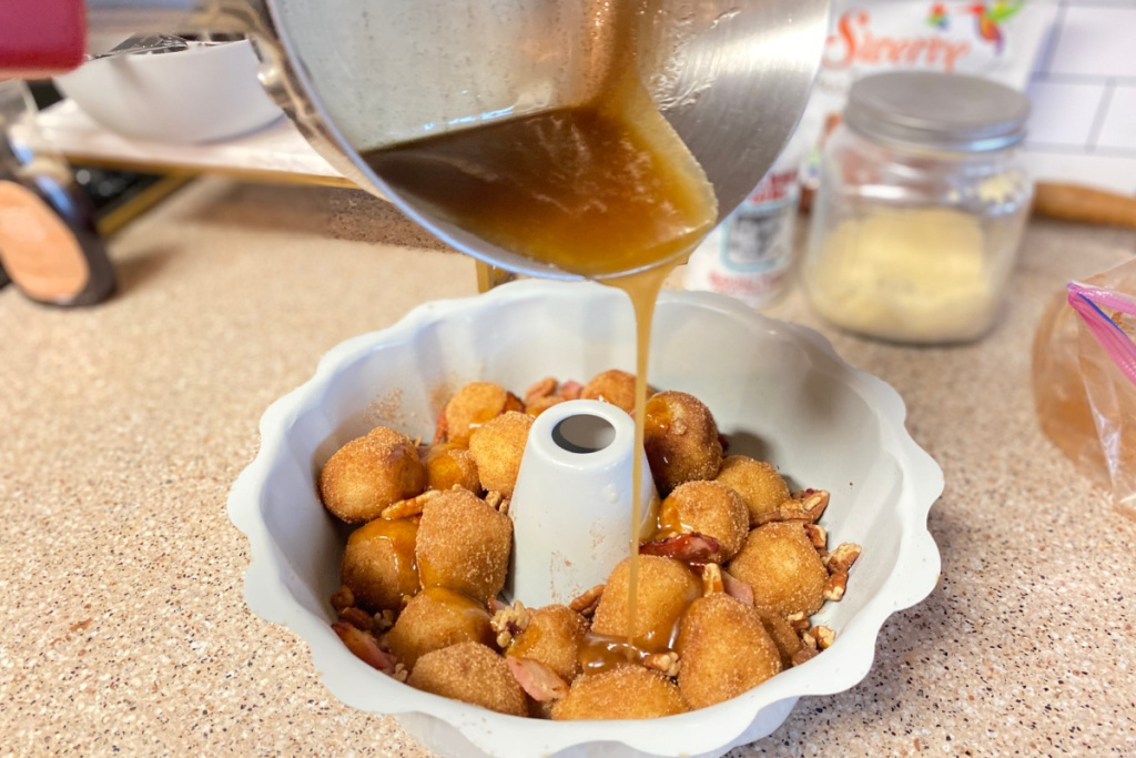 pouring sauce over keto monkey bread
