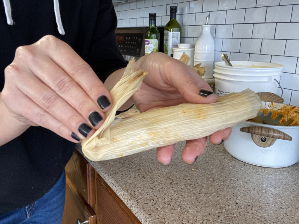 girl folding end of keto tamale