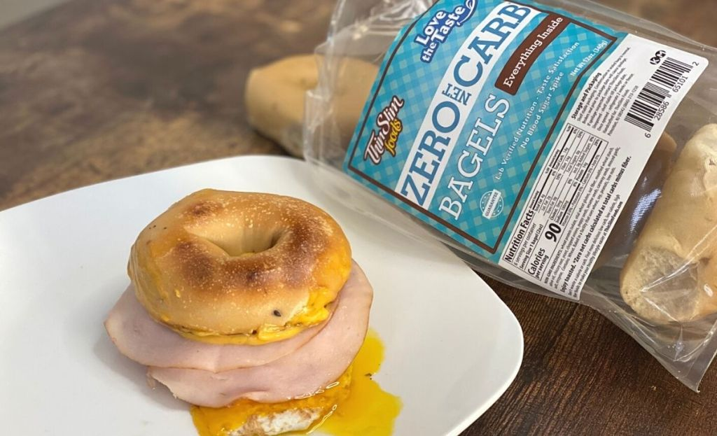 A bagel sandwich on a plate next to a bag of bagels