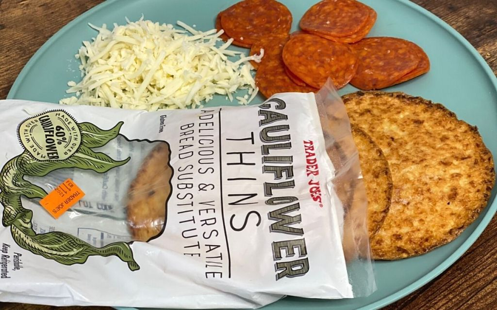 trader joe's cauliflower bread thins on a plate next to some cheese and pepperoni slices