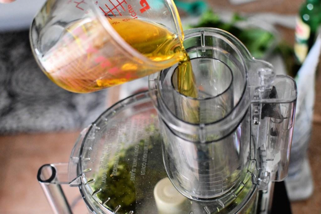 adding olive oil to pesto in food processor