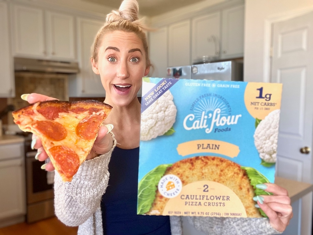 woman holding out slice of cauliflower crust pepperoni pizza