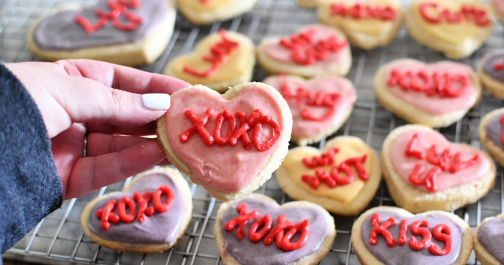 holding a keto conversation heart sugar cookie
