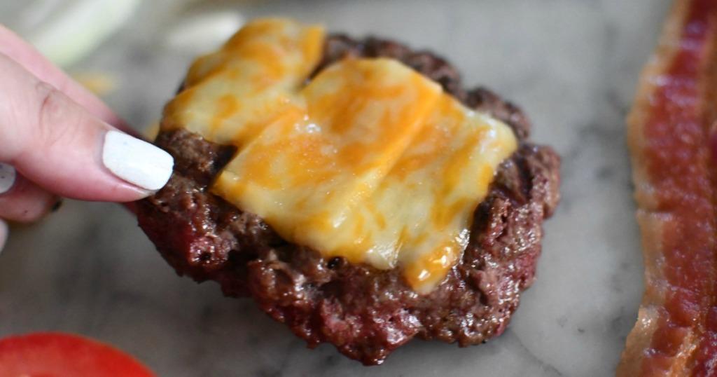 lifting bison burger with cheese