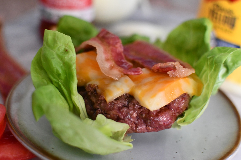burger on top of lettuce wrap with cheese