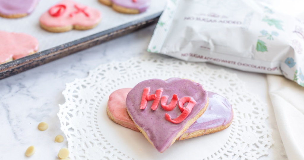 keto conversation heart sugar cookies on a plate next to tray