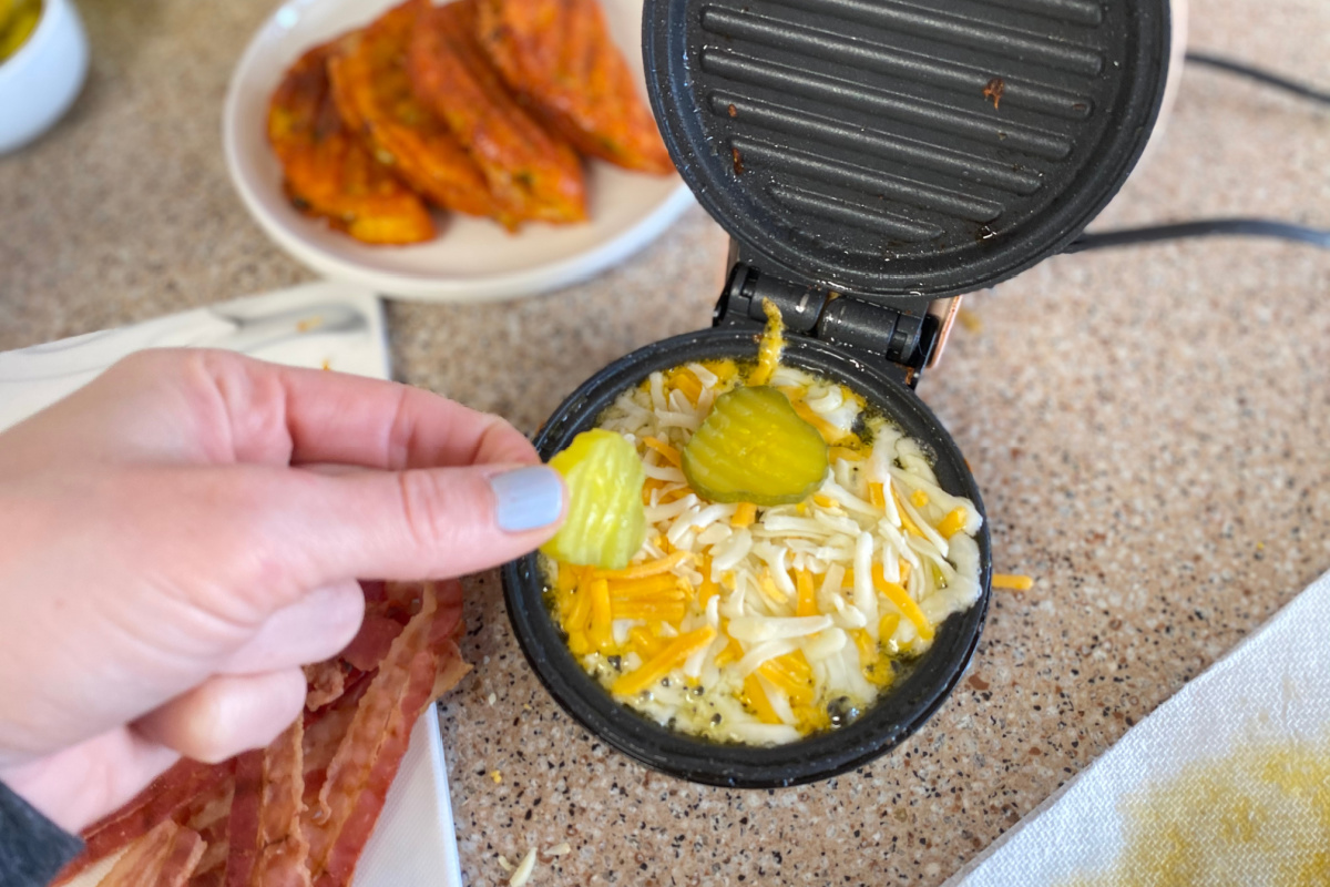 placing pickles into cheese waffle