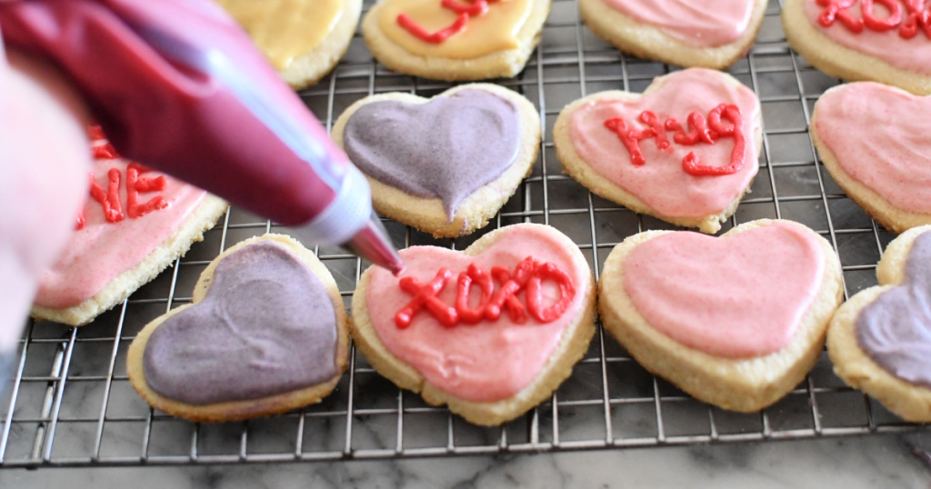 piping frosting on keto conversation heart sugar cookies