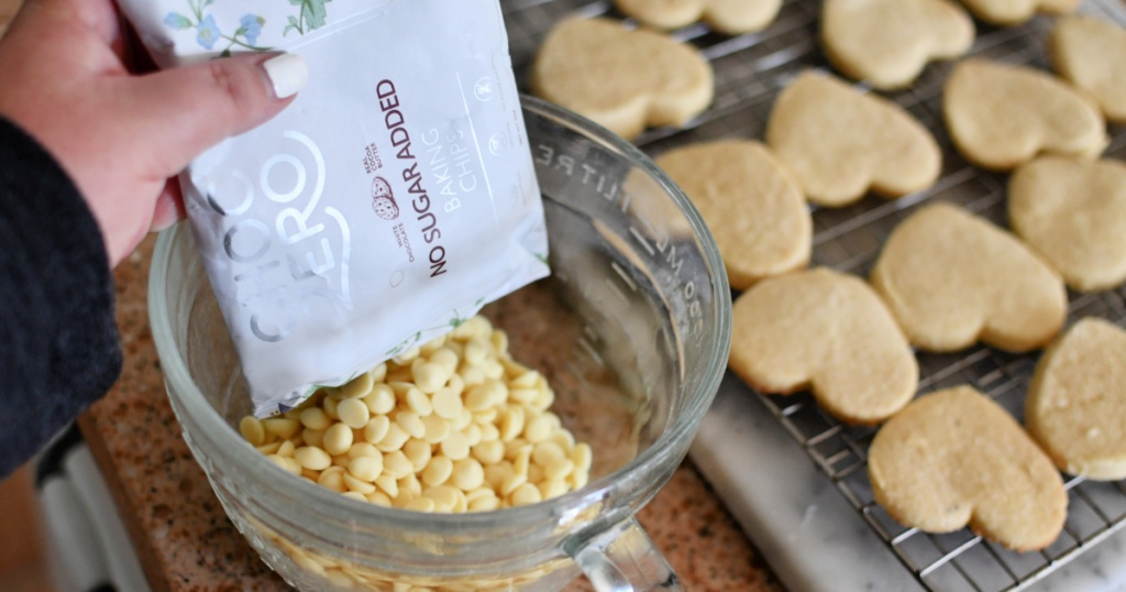 pouring choczero white sugar-free chocolate chips into a bowl