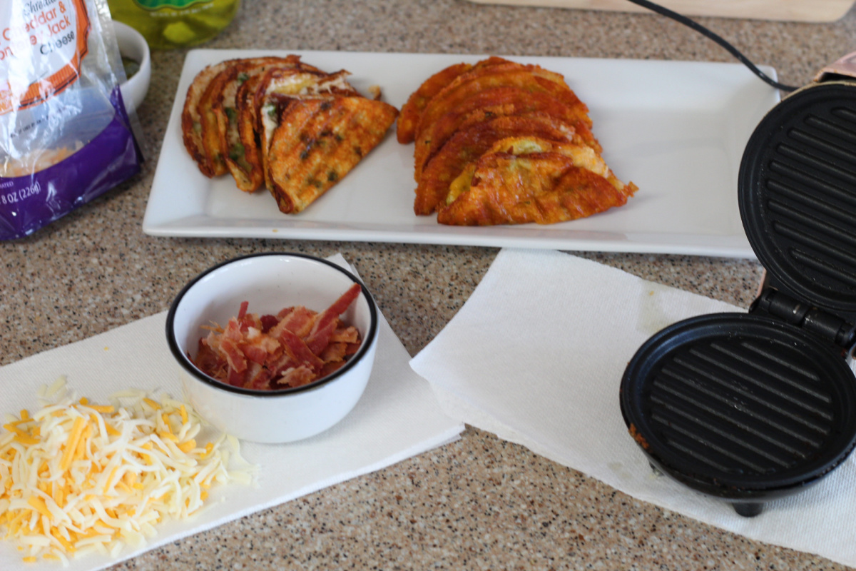 bacon and cheese on counter next to keto cheese waffles and DASH mini waffle maker