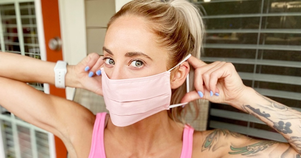 woman putting on pink face mask