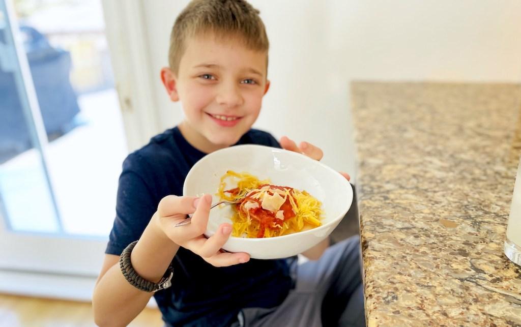 boy holding a bowl of yellow squash and marinara sauce