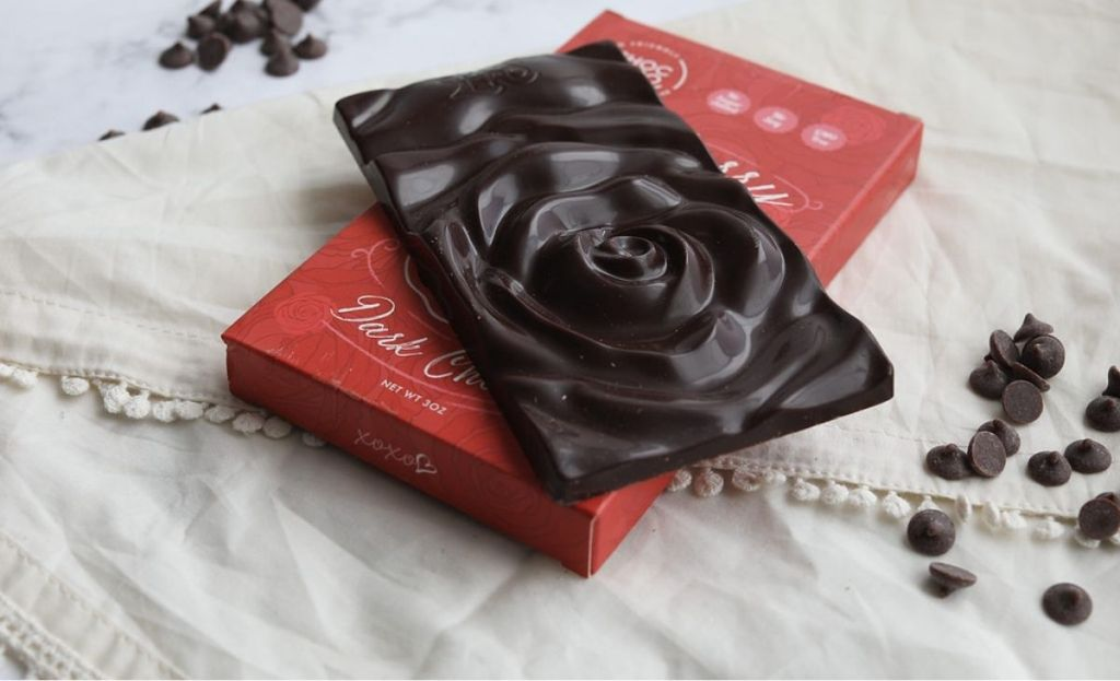 A rose-themed chocolate bar next to the package and some chocolate chips