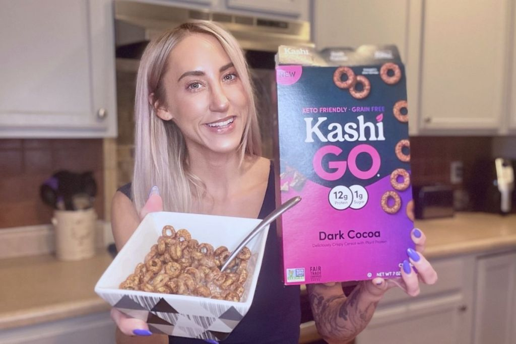 A woman holding a box of cereal and a bowl full of cereal