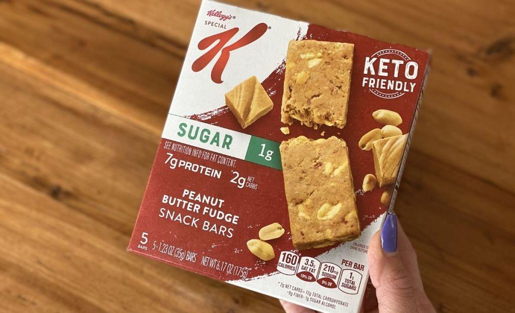 A hand holding a box of keto bars