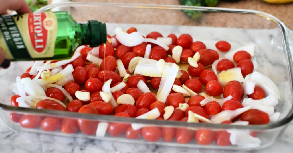 adding olive oil to tomatoes and feta