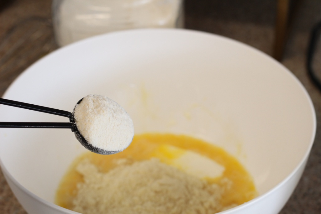 adding coconut flour to mixing bowl