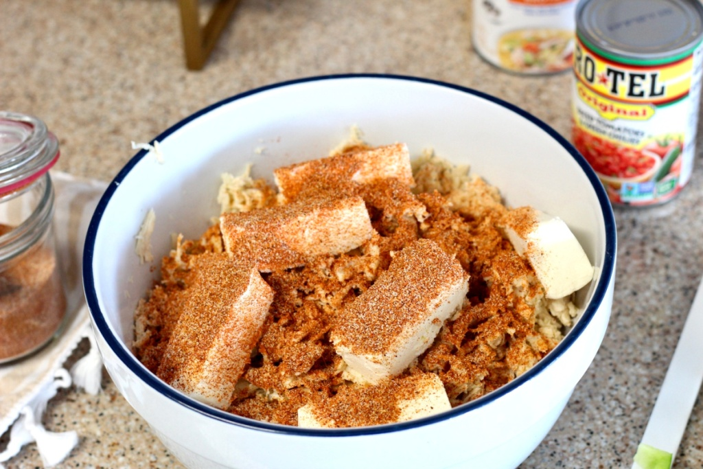 mixing cream cheese and taco seasoning into shredded chicken