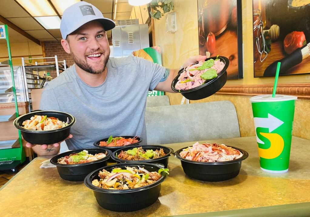 man holding subway protein bowls