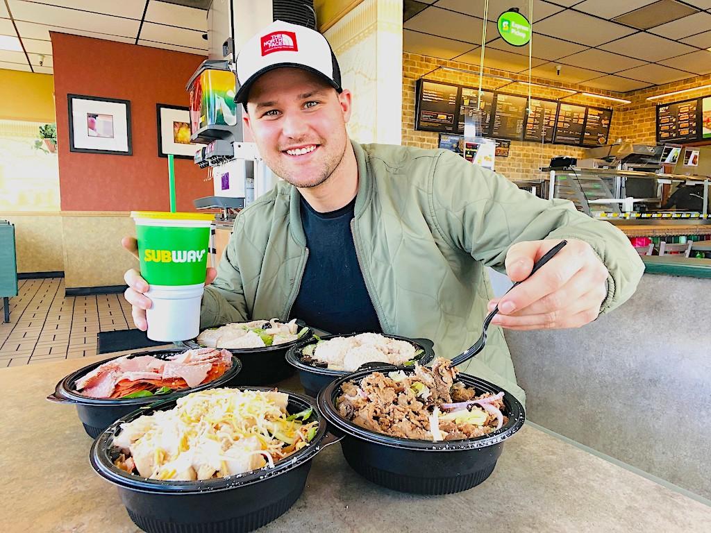 man inside Subway sampling 5 different protein bowls