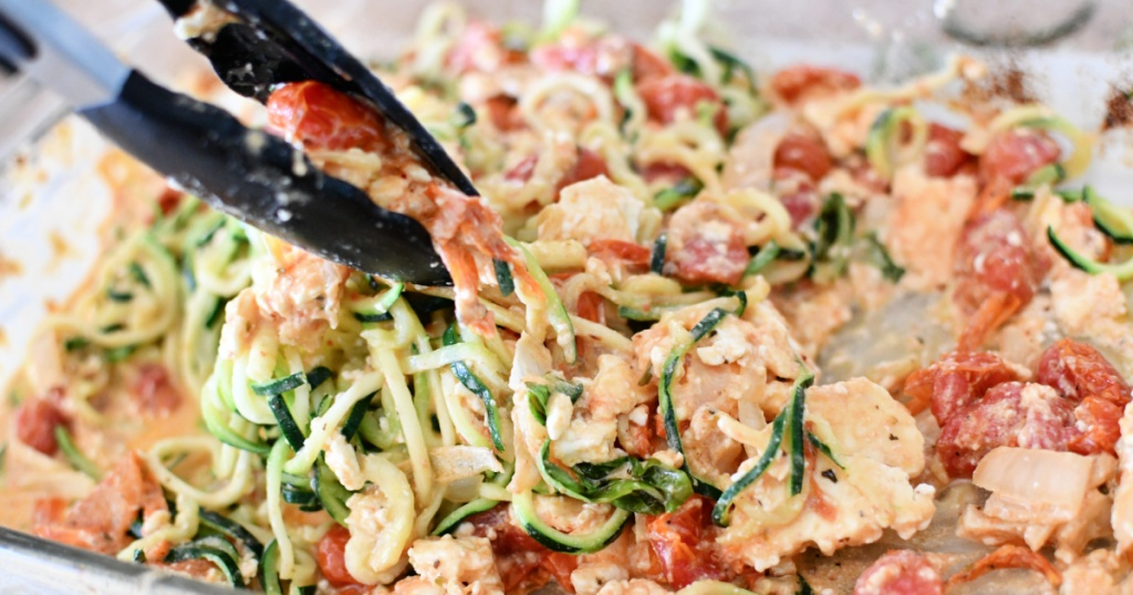 mixing zoodles with baked feta sauce