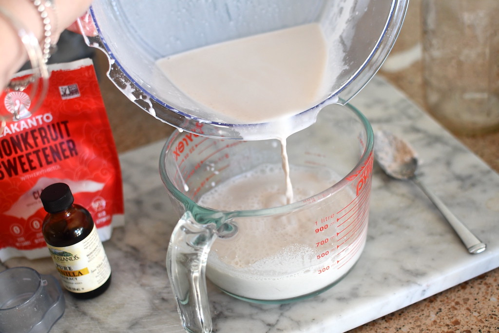 pouring almond milk into glass measuring cup