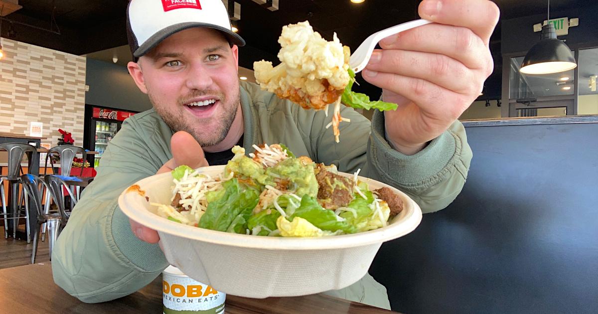 man holding Qdoba salad with cauliflower mash