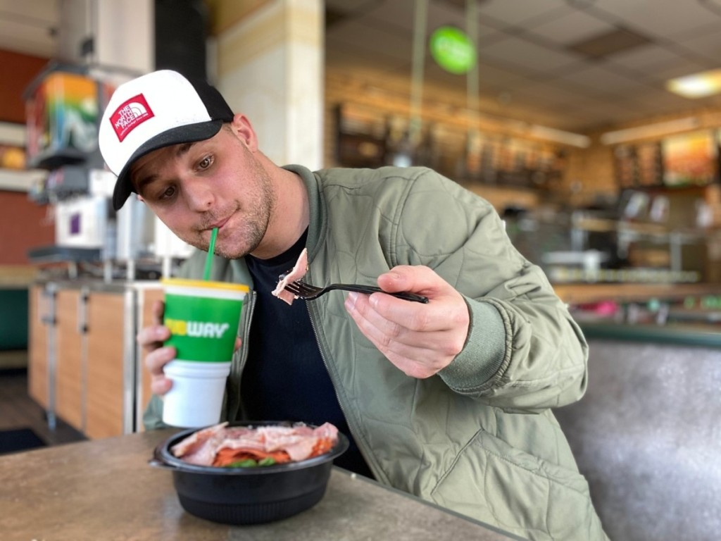 man holding Subway fountain drink and fork full of cold cuts